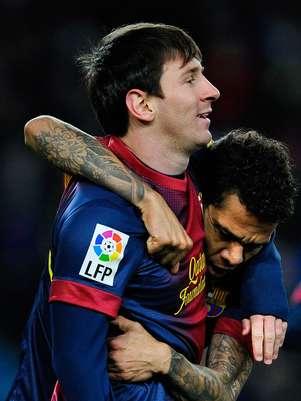 Lionel Messi recebe abraço de Daniel Alves; argentino deixou sua marca pela 15ª rodada consecutiva Foto: Getty Images