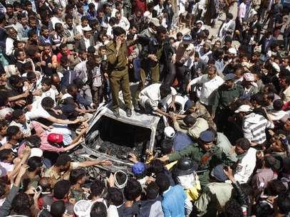 Militares e bombeiros tentam remover corpo carbonizado de táxi que foi incendiado após ser atingido durante o acidente Foto: Reuters