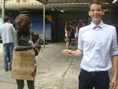 Na UFMG, jovem foi acorrentada, teve o corpo pintado e precisou carregar placa na qual se lê 'Caloura Chica da Silva' Foto: Facebook / Reprodução