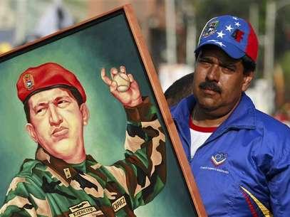 Nicolás Madurosegura pintura do ex-presidente Hugo Chávez durante comício Foto: Carlos Garcia Rawlins / Reuters