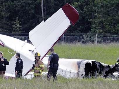 Policiais revistam destroços do avião após acidente Foto: AP