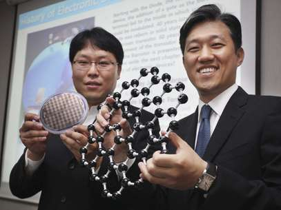 Dois pesquisadores da Samsung Electronics Co., o maior fabricante mundial de chips de memória para dispositivos de informática, apresentam a estrutura de um novo transístor fabricado com grafeno Foto: EFE