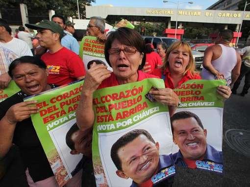 Manifestantes celebram o retorno de Chávez a Venezuela em frente ao hospital em que ele está internado  (Foto: AP)