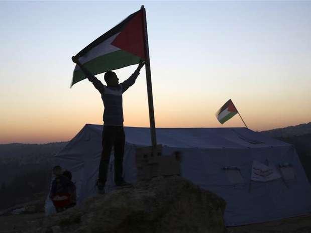 Ativista segura bandeira palestina perto de uma tenda recém montada no vilarejo de Beit Iksa, na Cisjordânia, entre Ramallah e Jerusalém Foto: Mohamad Torokman / Reuters