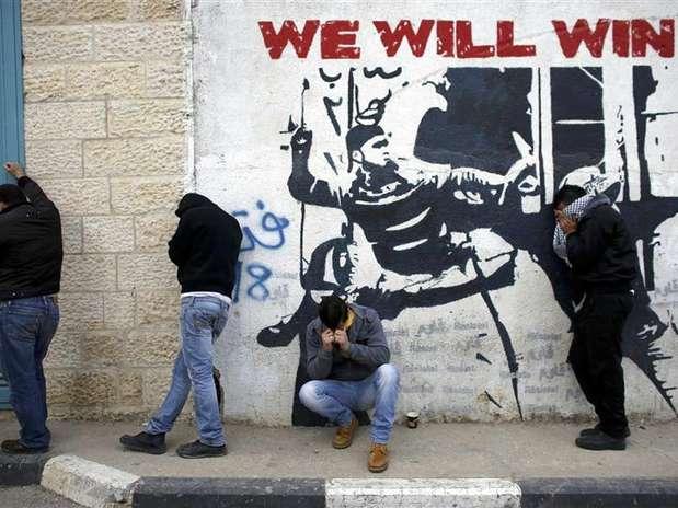Palestinos que atiravam pedras protegem-se do gás lacrimogêneo lançado por forças de segurança israelenses durante confrontos em campo de refugiados em Belém, na Cisjordânia. Palestinos saudaram um relatório do Conselho de Direitos Humanos da ONU altamente crítico aos assentamentos judaicos na Cisjordânia ocupada, dizendo que isso justificava sua luta contra Israel. 24/01/2013 Foto: Ammar Awad / Reuters