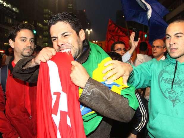 Manifestante morde bandeira do PT durante protesto em São Paulo Foto: Marcos Bezerra / Futura Press