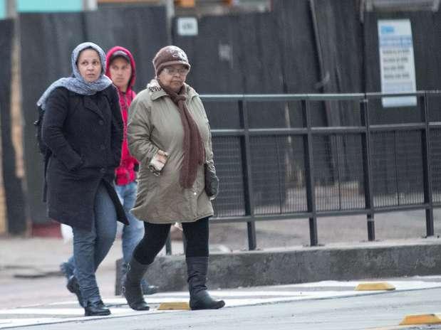 Casacos, mantas e gorros ajudaram a proteger do frio aqueles que precisaram sair cedo nesta sexta-feira em Porto Alegre (RS) Foto: Luciano Leon / Futura Press
