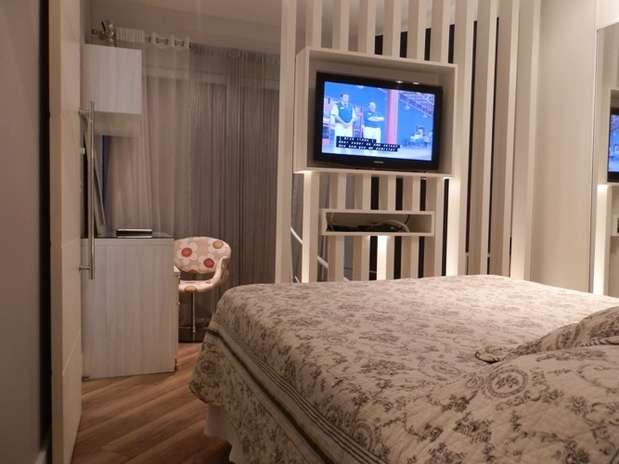 A arquiteta criou um painel que serve como divisória e nicho para TV. Foto: Andrade Mello Arquitetura