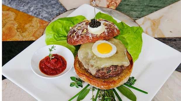 Le Burger Extravagant - O que é preciso para fazer hambúrguer mais caro do mundo? Carne waygu japonesa, infundida com manteiga de 10 erva e trufa branca, temperada com sal do Pacífico Alderwood, coberto de queijo cheddar, raspas de trufas negras e um ovo de codorna frito, servida com manteiga de trufa branca Campagna roll e finalizada com blini, creme fraiche e caviar Kaluga. Ah, e não se pode esquecer o diamante sólido incrustado no palito de ouro sobre o sanduíche. O prato sai por US$ 293 (cerca de R$ 595) e é servido apenas com hora marcada também no Serendipity 3, de Nova York, mundialmente famoso pelos valores caríssimos de seus pratos Foto: Reprodução
