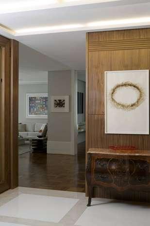Como esse hall tem muitas portas, Marcelo Rosset quis sumir com elas com um painel de madeira igual à madeira utilizada nelas Foto: Marco Antônio