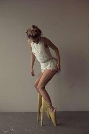 O sapato deixa os pés em um ângulo de 90°, virados para baixo, como em uma aula de balé, e as pernas em 45° para frente, apoiadas nos saltos dianteiros que se encaixam nas canelas Foto: Lyall Coburn / Divulgação