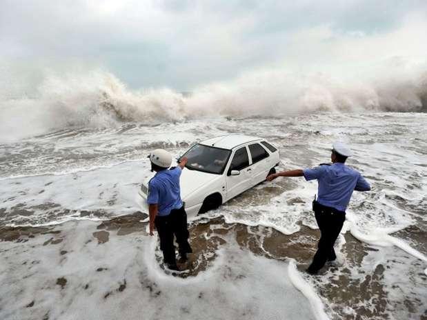 Policiais ajudam motorista a remover o carro da praia após ondas avançarem deviso ao tufão Bolaven, em Qingdao, na China Foto: AFP