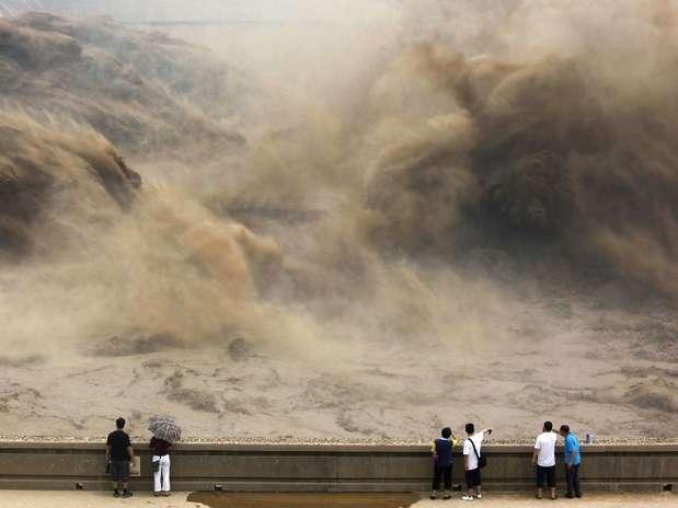 Visitantes observam uma represa ser aberta no rio Amarelo, em Jiyuan, na China Foto: AFP