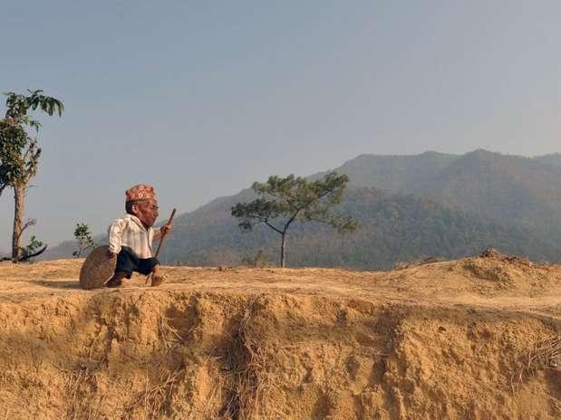 o nepalês Chandra Bahadur Dangi, 72 anos, que diz ser o menor homem do mundo, caminha perto da casa dele, em Reemkholi Foto: AFP