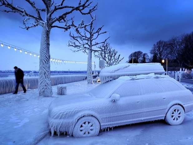 Homem passa por um carro coberto por gelo no lago Geneva, em Versoix, na Suíça Foto: AFP