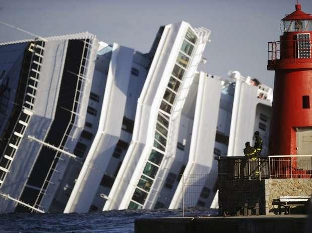 Bombeiros observam o navio cruzeiro Costa Concordia, que naufragou perto da ilha de Giglio, na Itália Foto: AFP