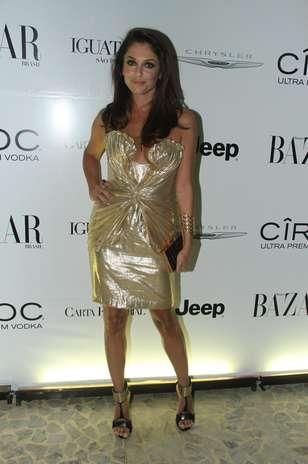 A modelo Camila Guebur usa vestido dourado com detalhes drapeados e ainda aposta em maxiacessórios, como as sandálias pesadas e o bracelete Foto: Amauri Nehn / Agência Senado