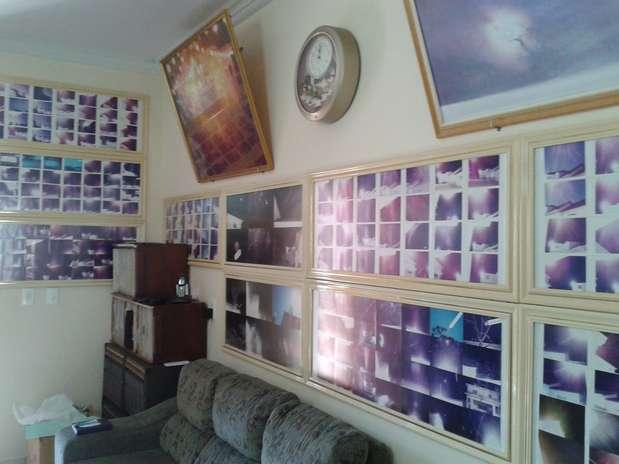 """Na sala de estar da casa de Hirota, é possível ver fotos do Sol reveladas em negativo que ele diz serem noturnas e da manifestação de um \""""espírito de luz\"""" Foto: Diogo Alcântara / Terra"""