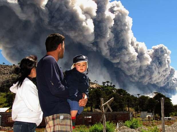 Família observa nuvem de fumaça e cinzas expelida pelo vulcão Copahue, em Caviahue, na província argentina de Neuquén, cerca de 1,5 mil km distante de Buenos Aires. As autoridades do Chile e da Argentina emitiram alerta devido à atividade do vulcão, localizado na fronteira entre os países  Foto: AFP