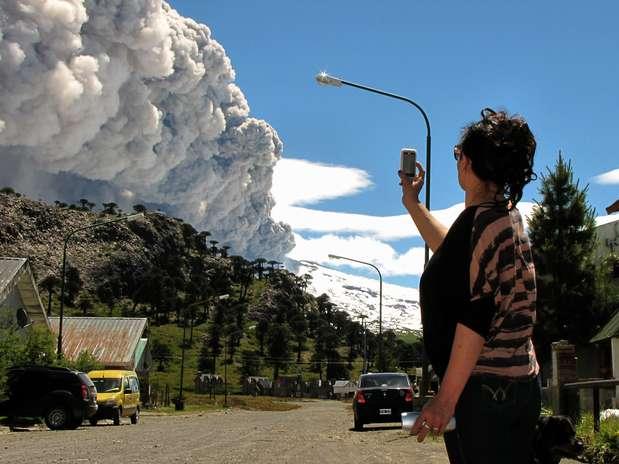 Mulher fotografa a atividade do vulcão Foto: AFP