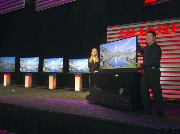 Modelos posam ao lado de TV Ultra HD; à esquerda, é possível ver uma LED Smart 3D TV da Sharp Foto: Reuters