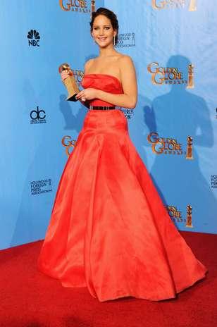 Jennifer Lawrence vestiu Dior Haute Couture para a noite do Globo de Ouro. A atriz arrematou o vestido em tom alaranjado tomara-que-caia com um cinto prateado, que valorizou suas curvas Foto: Getty Images