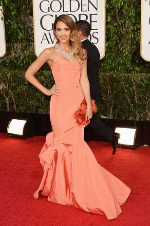 Jessica Alba optou por um Oscar de la Renta coral, que complementou com um maxicolar. Fios ondulados e batom combinando com o vestido completaram o look Foto: Getty Images