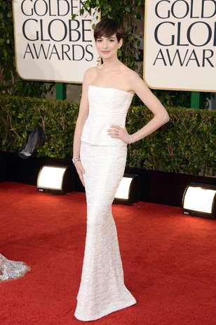 Anne Hathaway compôs um look bastante minimalista e elegante: vestido Chanel de duas peças levemente brilhante com pulseiras e brincos discretos Foto: Getty Images