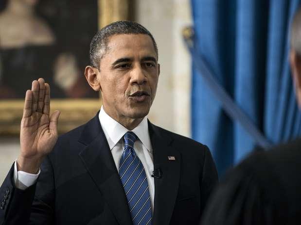 O presidente Barack Obama levanta o braço direito e faz o juramento diante do juiz John Roberts, presidente da Suprema Corte Foto: AP